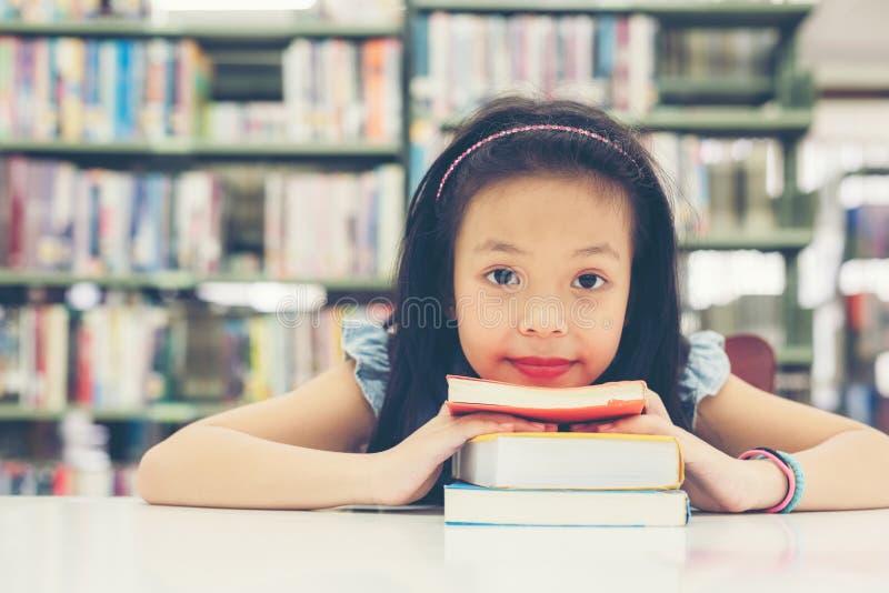 Livros de leitura bonitos asiáticos de sorriso da menina das crianças para a educação e para ir educar na biblioteca fotografia de stock