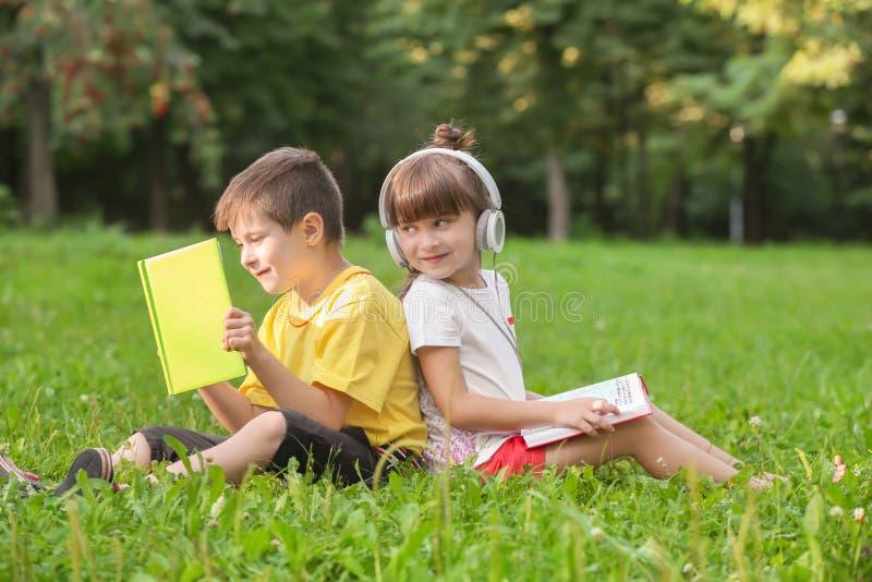 Livros de leitura bonitos das crianças pequenas e escuta a música no parque no dia de verão imagens de stock