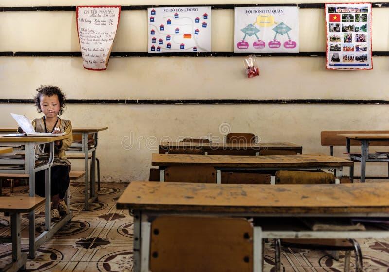 Livros de leitura da menina dentro da sala de aula em uma vila pequena, Sapa, Vietname foto de stock