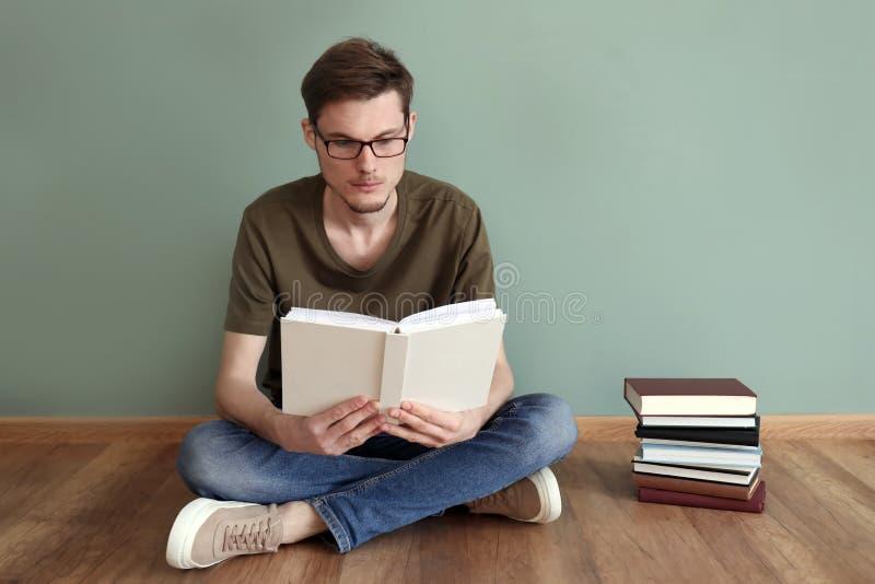 Livros de leitura do homem novo ao sentar-se no assoalho perto da parede da cor fotografia de stock royalty free
