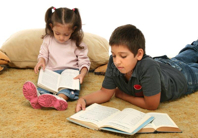 Livros de leitura do irmão e da irmã no assoalho imagens de stock royalty free