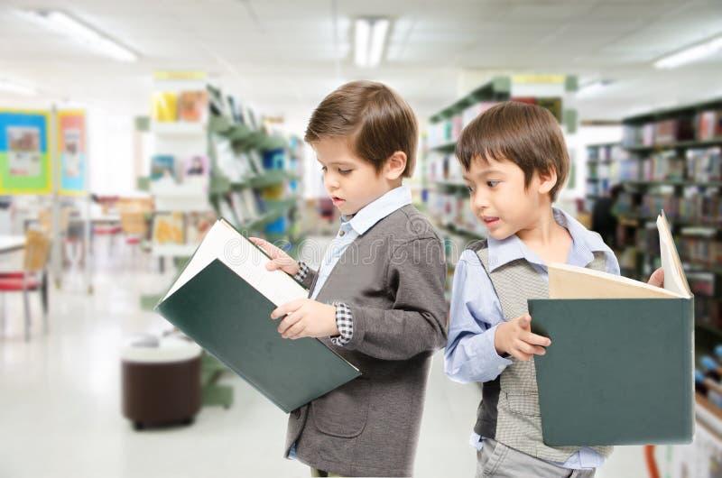 Livros de leitura do rapaz pequeno junto no fundo branco foto de stock