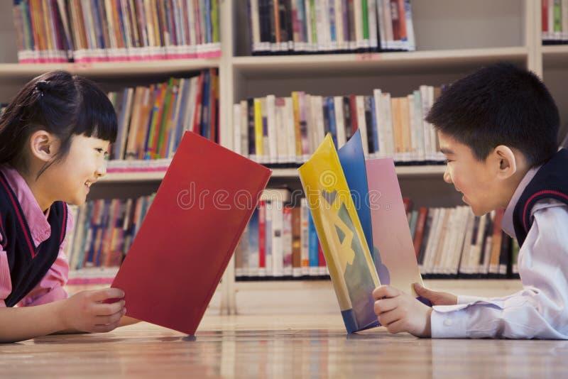 Livros de leitura dos alunos na biblioteca foto de stock
