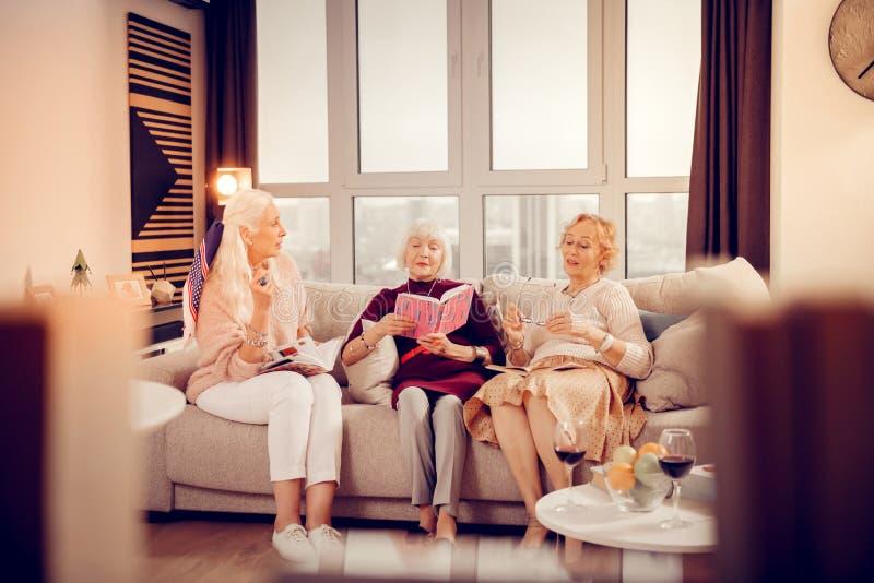 Livros de leitura envelhecidos agradáveis das mulheres em casa foto de stock royalty free