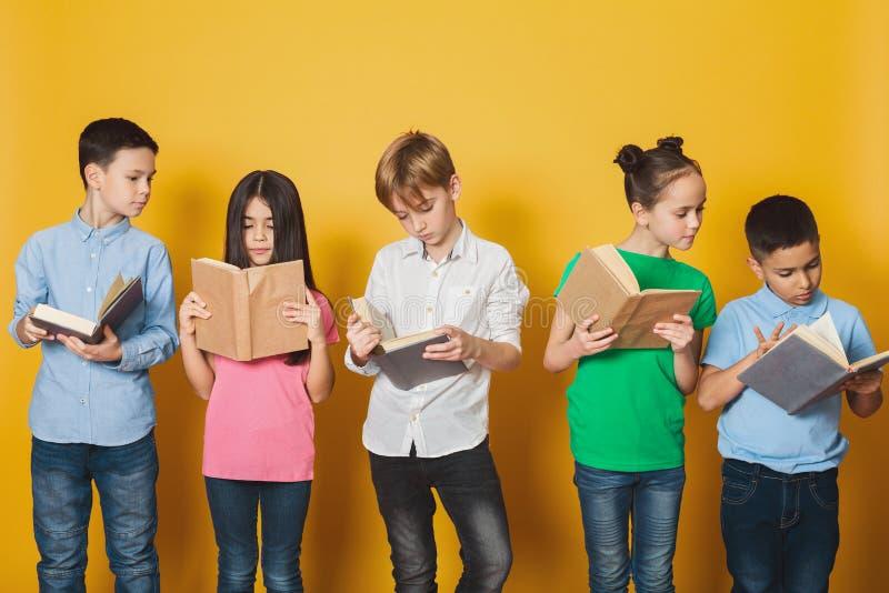 Livros de leitura espertos das crianças perto da parede amarela imagens de stock royalty free