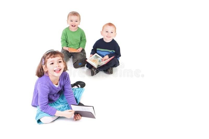 Livros de leitura felizes dos miúdos fotos de stock royalty free