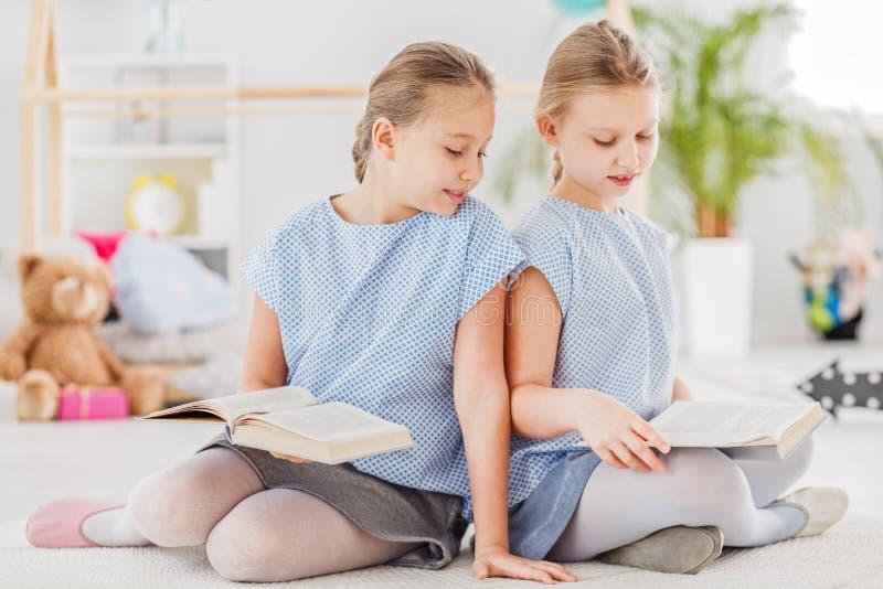 Livros de leitura louros das meninas fotos de stock