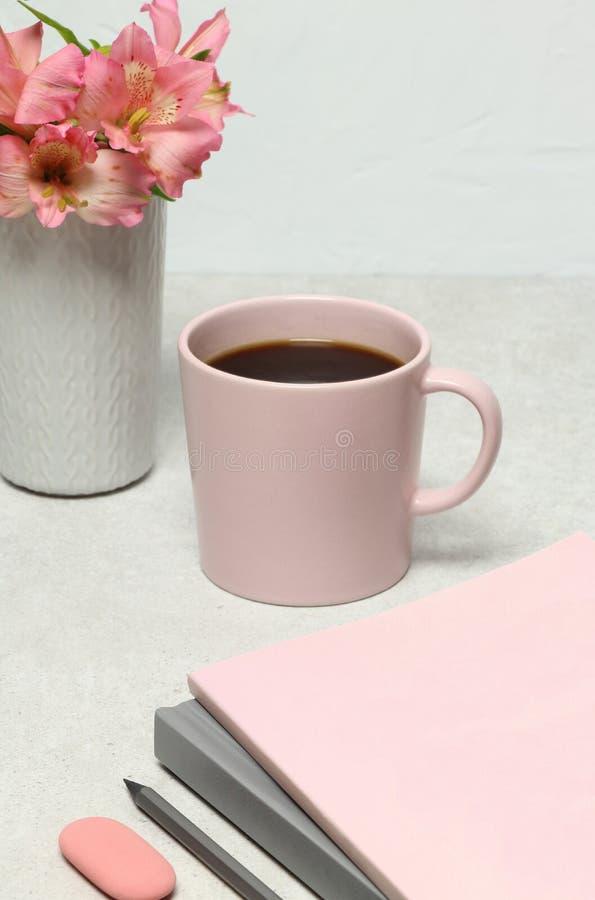 Livros de nota, lápis, copo de café, flores do ramalhete na tabela de pedra fotografia de stock