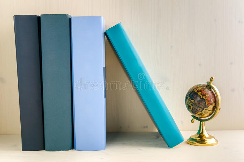 Livros do livro encadernado e um globo em uma prateleira foto de stock