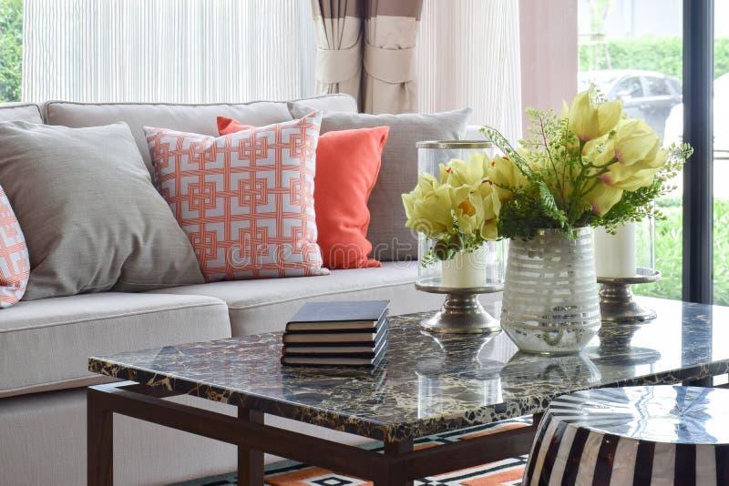 Livros e artigos decorativos na tabela superior de mármore e no grupo vívido do sofá imagens de stock