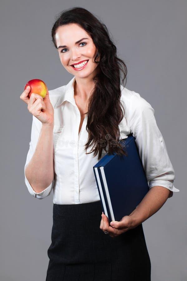 Livros e maçã da terra arrendada da mulher imagens de stock royalty free