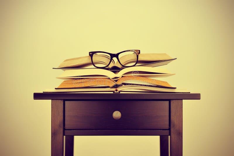 Livros e monóculos em uma mesa, com um efeito retro fotos de stock royalty free