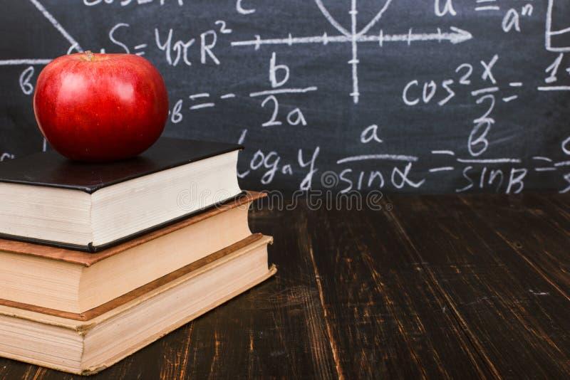 Livros e uma ma?? em uma tabela de madeira, na perspectiva de um quadro com f?rmulas Teacher' conceito do dia de s e de volt fotografia de stock