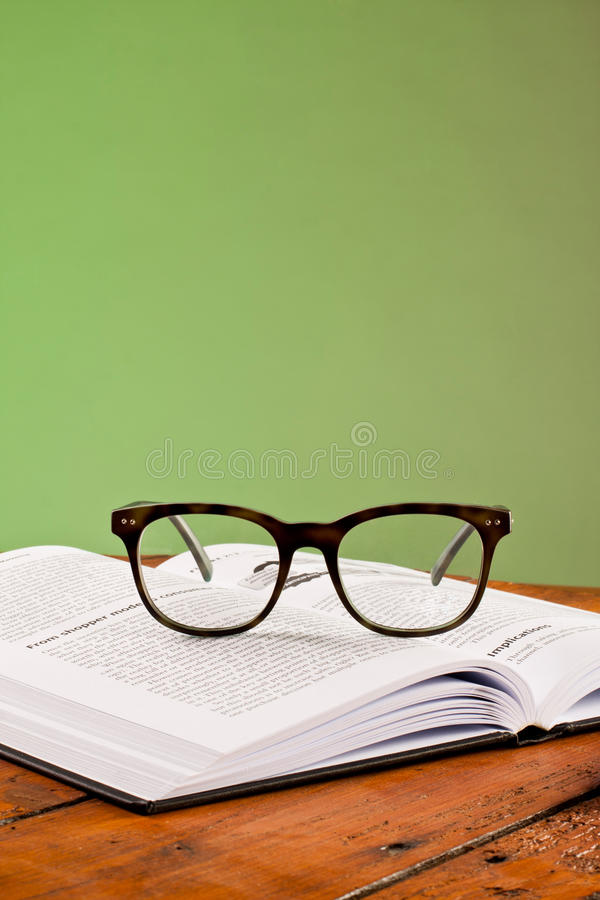 Livros e vidros em uma tabela de madeira fotos de stock