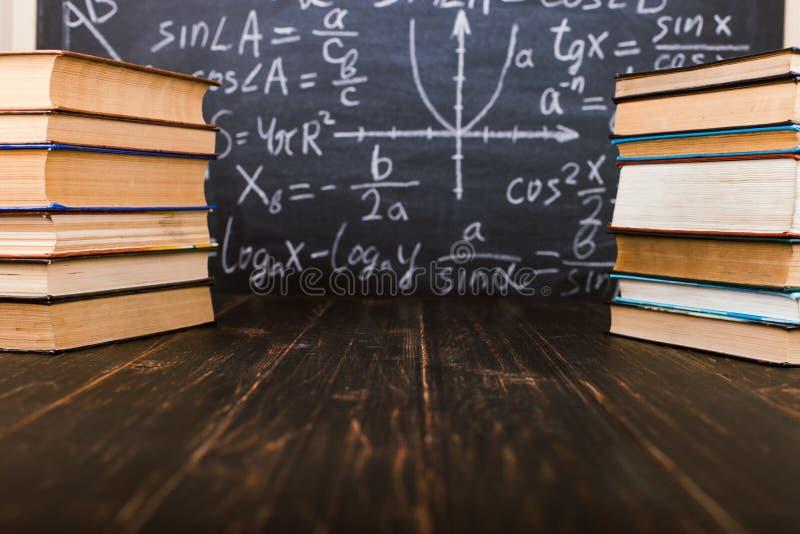 Livros em uma tabela de madeira, na perspectiva de uma placa de giz com f?rmulas Teacher' conceito do dia de s e de volta ?  fotografia de stock
