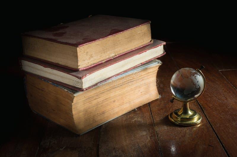 Livros empoeirados velhos com globo de vidro imagem de stock
