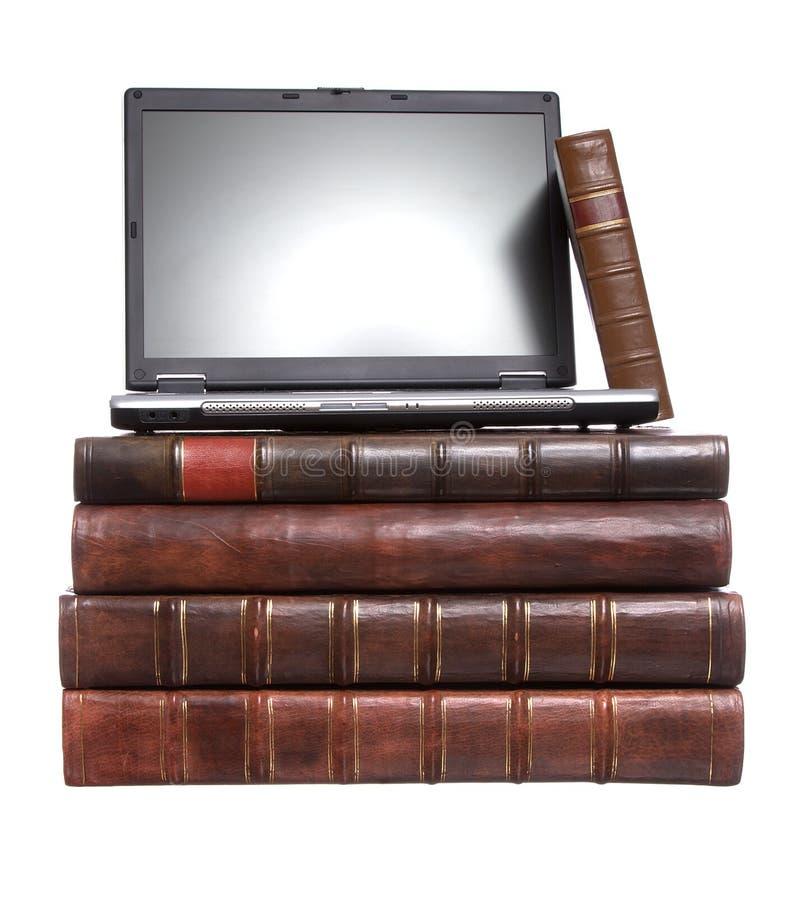 Livros encadernados de couro velhos com um portátil fotos de stock