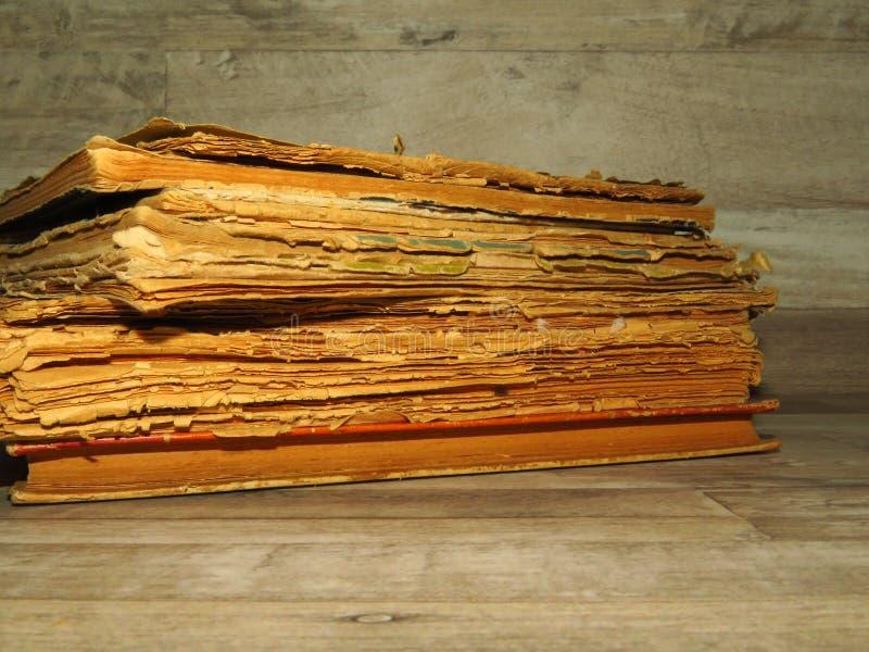 Livros esfarrapados muito velhos no fundo rústico da madeira do estilo do vintage imagens de stock