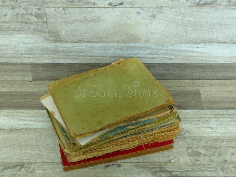 Livros esfarrapados muito velhos no fundo rústico da madeira do estilo do vintage foto de stock