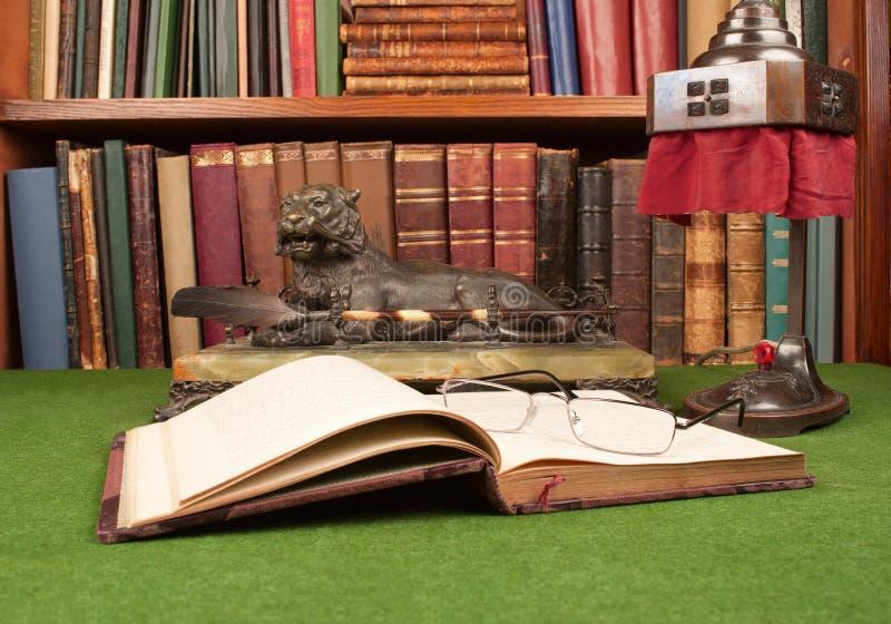 Livros, lâmpada, tinteiro e vidros de leitura de couro antigos fotografia de stock