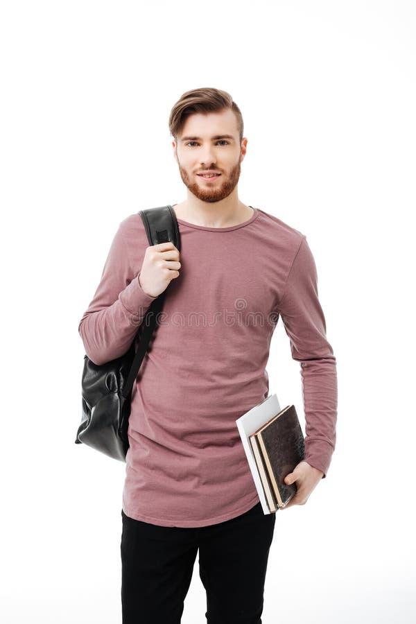 Livros levando consideráveis do estudante masculino e uma trouxa isolada imagens de stock royalty free