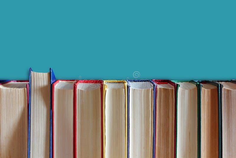 Livros na capa dura em um fundo azul imagens de stock
