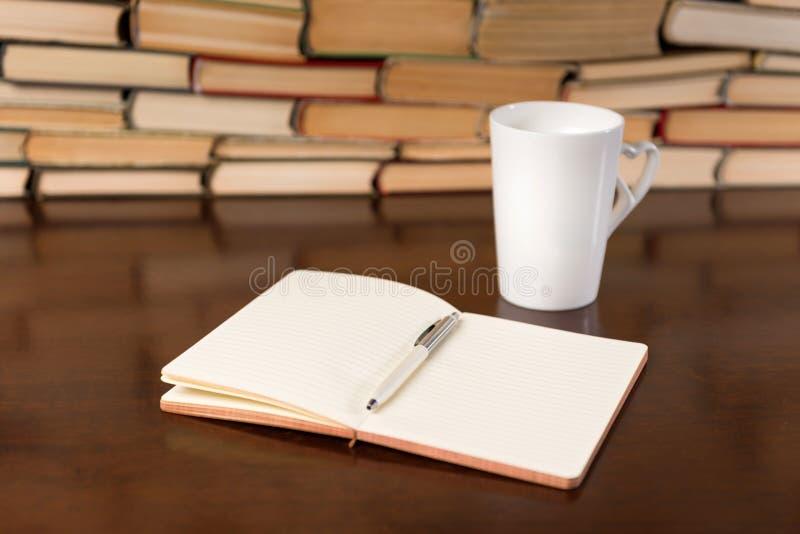 Livros na tabela de madeira com chá e o caderno aberto fotos de stock royalty free
