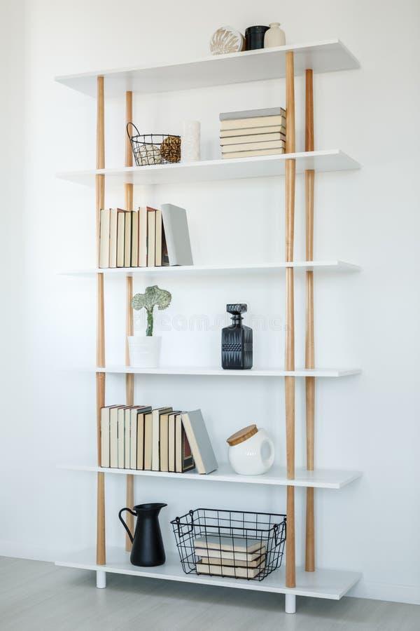 Livros nas prateleiras de madeira brancas no interior simples da sala de visitas Re fotografia de stock royalty free
