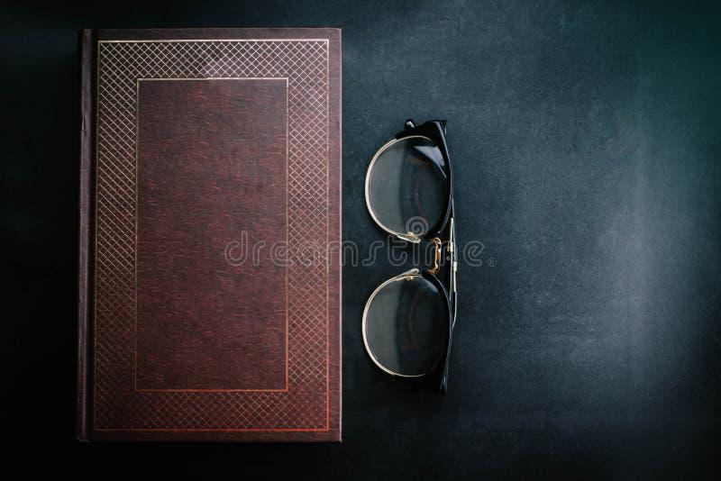 Livros velhos com vidros em um fundo preto fotografia de stock royalty free