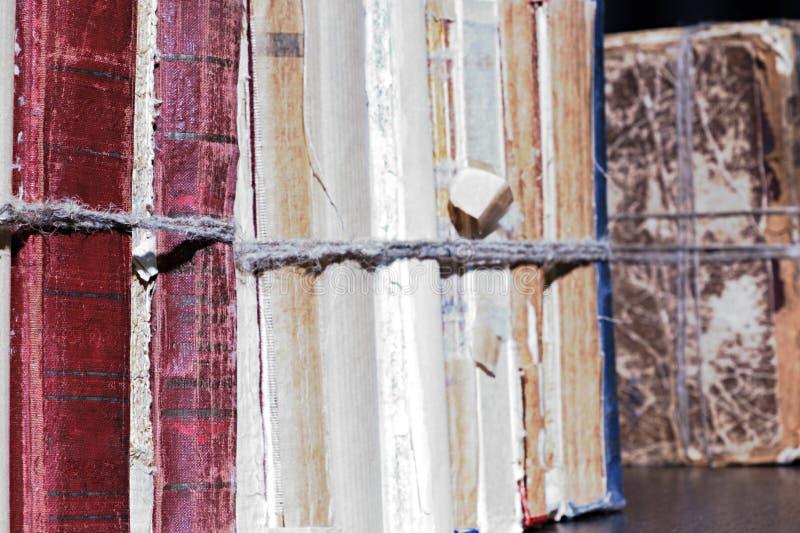 Livros velhos do close-up amarrados com uma corda na prateleira de madeira na biblioteca ou no arquivo fotos de stock royalty free