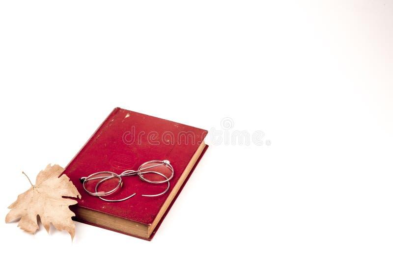 Livros velhos do vintage, licença de outono e vidros isolados nos vagabundos brancos fotos de stock