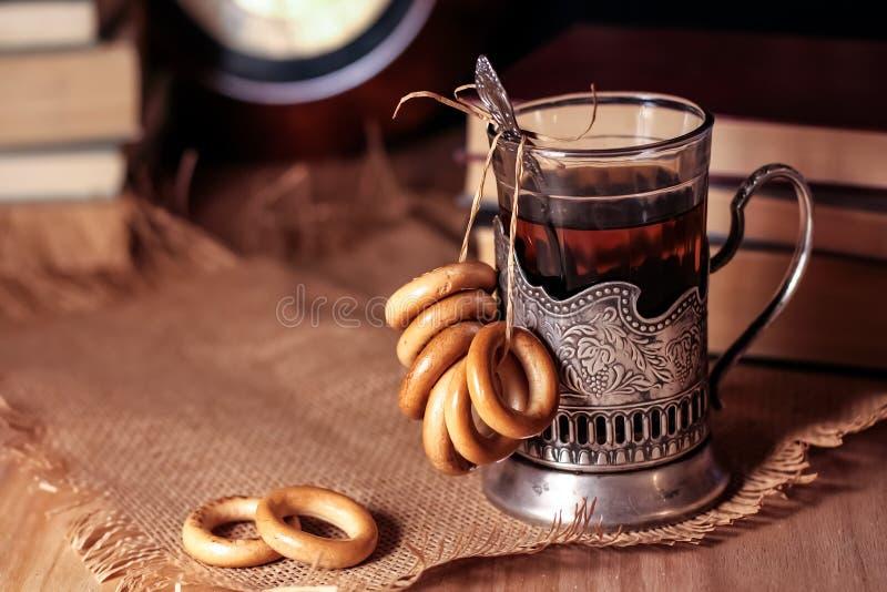 Livros velhos e chá na noite Um vidro da bebida na tabela E fotografia de stock