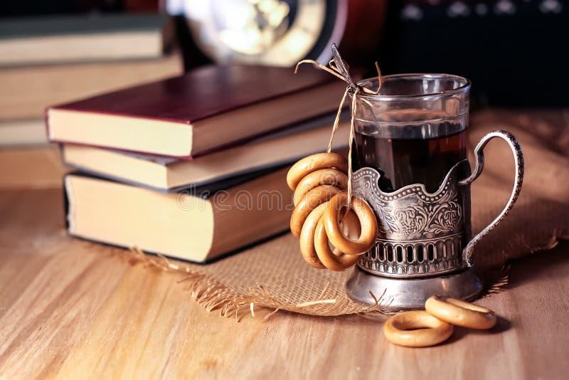 Livros velhos e chá na noite Um vidro da bebida na tabela E imagem de stock royalty free