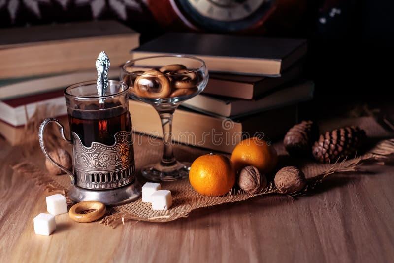 Livros velhos e chá na noite Um vidro da bebida na tabela E fotos de stock