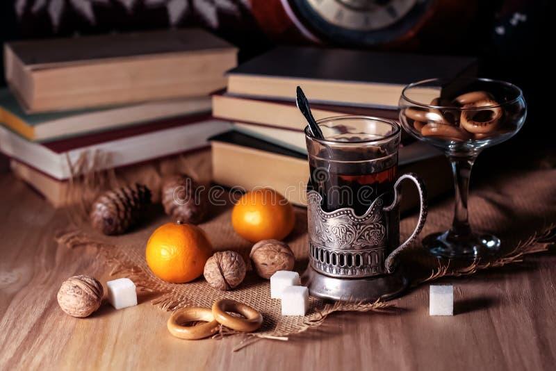 Livros velhos e chá na noite Um vidro da bebida na tabela E foto de stock