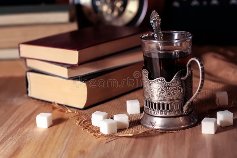 Livros velhos e chá na noite Um vidro da bebida na tabela E imagem de stock