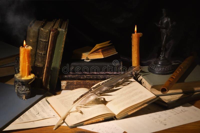 Livros velhos e velas na tabela de madeira imagens de stock