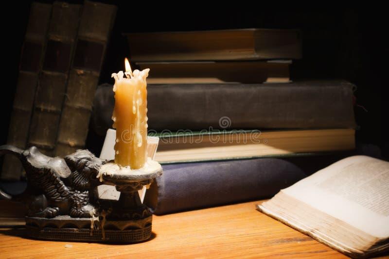 Livros velhos e velas na tabela de madeira imagens de stock royalty free