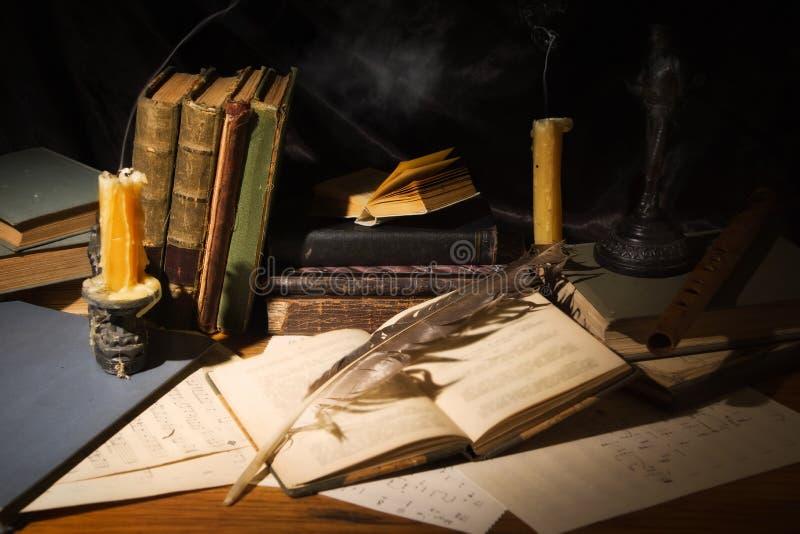 Livros velhos e velas na tabela de madeira imagem de stock