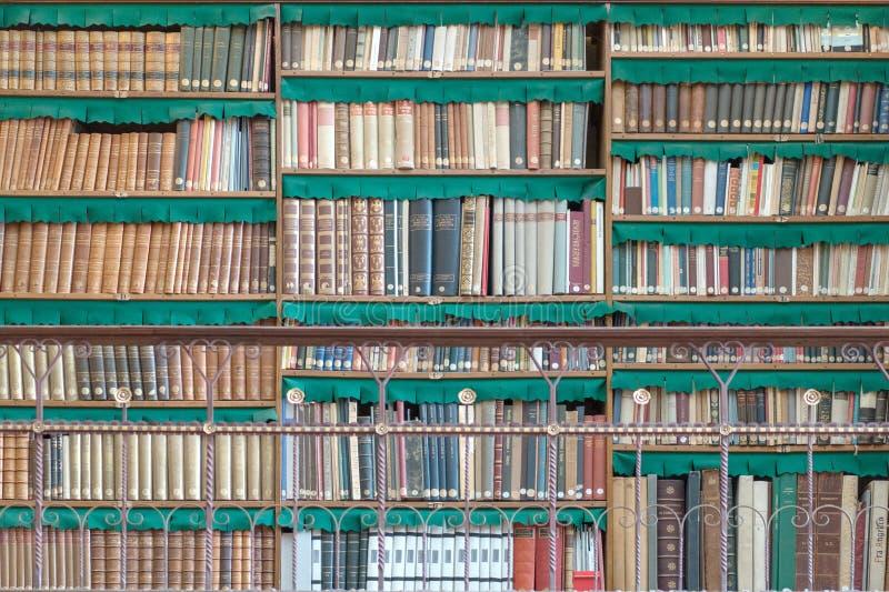 Livros velhos em prateleiras da biblioteca imagens de stock royalty free