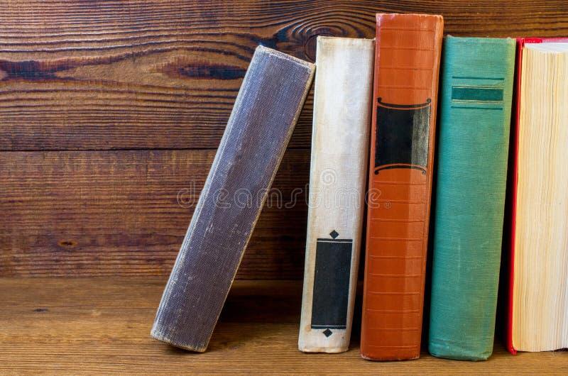 Livros velhos empilhados em uma prateleira de madeira imagem de stock royalty free