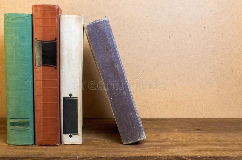 Livros velhos empilhados em uma prateleira de madeira imagem de stock