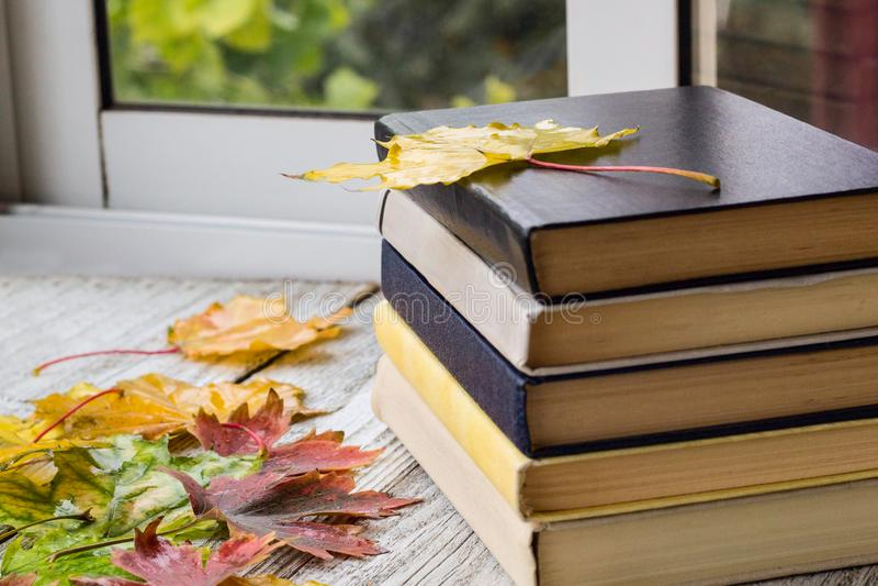 Livros velhos nas folhas de outono no fundo de madeira imagem de stock royalty free