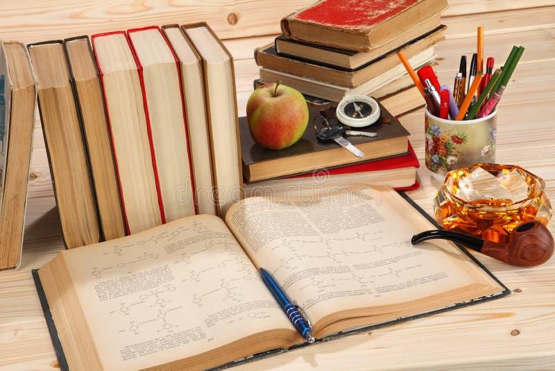 Livros velhos, tubulação de fumo, cinzeiro, compasso, copo com penas imagens de stock