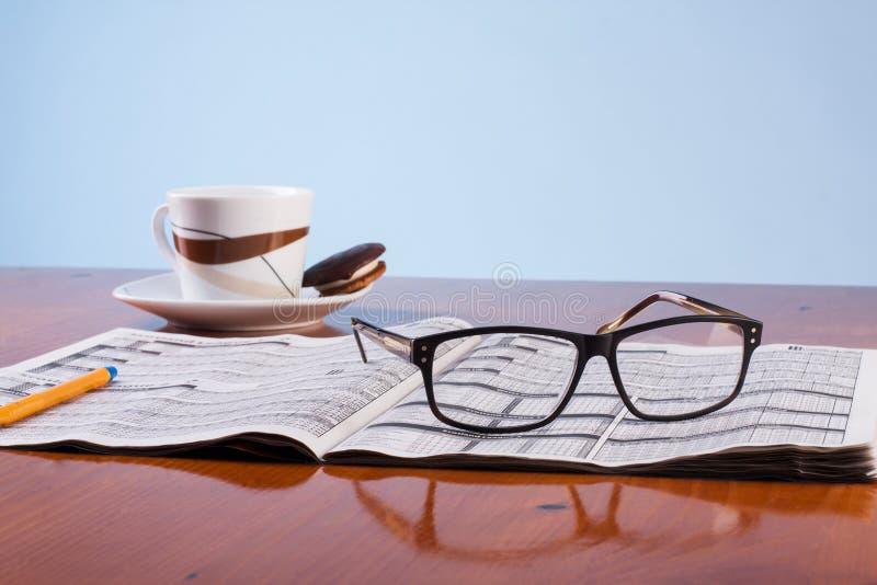 Livros, vidros e xícara de café em uma tabela de madeira fotografia de stock royalty free