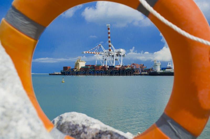 Livsäkerhetscirkel och lastfartyg på hamnstaden arkivbilder