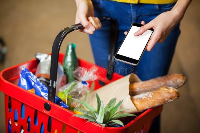 Livsmedel och mobiltelefon för kvinna hållande i supermarket arkivbild