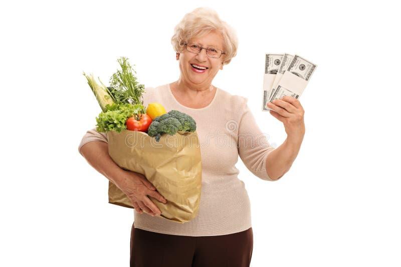 Livsmedel och pengar för mogen dam hållande royaltyfri bild