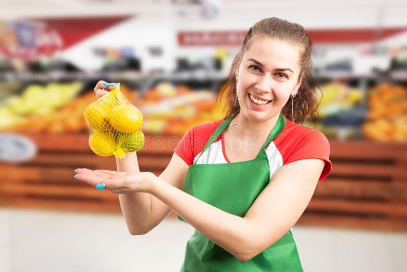 Livsmedelsbutikanställd som framlägger påsen av citroner arkivfoton
