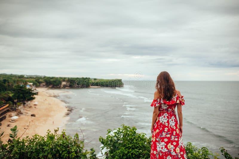 Livsstil för familjsemester Sällsynt sikt av brunettkvinnan i röd klänningställning på synvinkeln Se den Balangan stranden från h royaltyfria foton